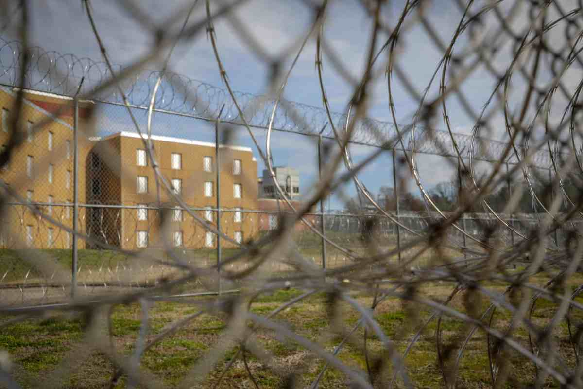 shows a brick building of Central Prison behind a chain link fence topped by razor wire