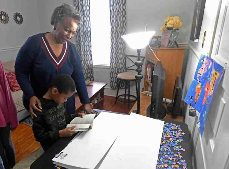 shows an older Black woman standing over a little buy who's sitting at a desk and is reading from a book