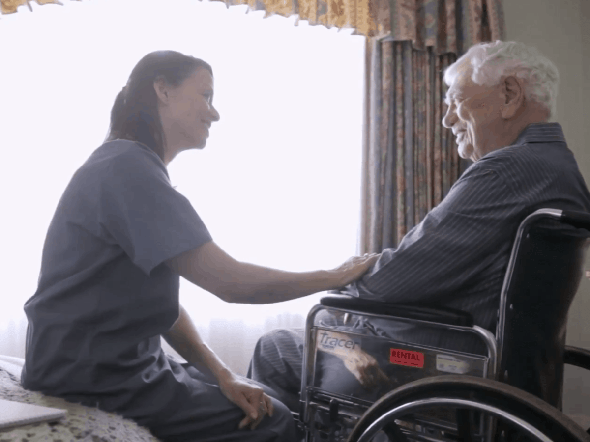 Shows a young woman sitting with an older man who is in a wheelchair, likely homebound