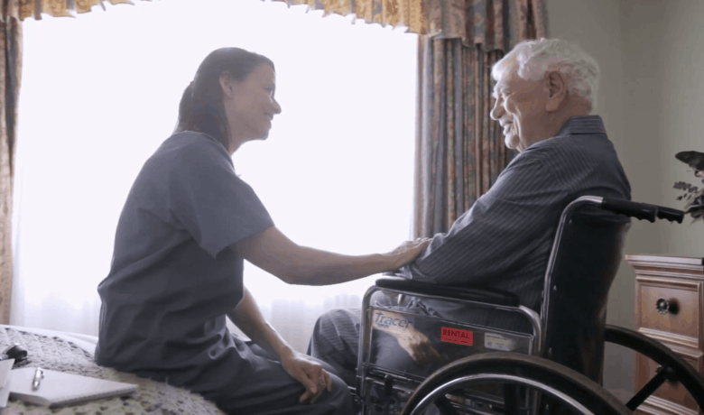 Shows a young woman sitting with an older man who is in a wheelchair