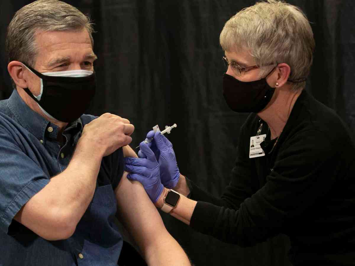 shows a man with a mask on rolling up his sleeve and receiving a COVID vaccine in his left arm as he looks ahead.