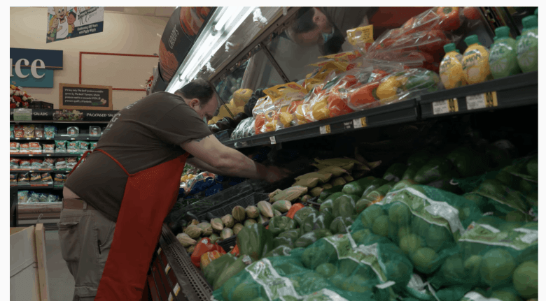 Shows a man wearing a red apron over his uniform and a facemask to prevent COVID arranging vegetables on refrigerated produce shelves.