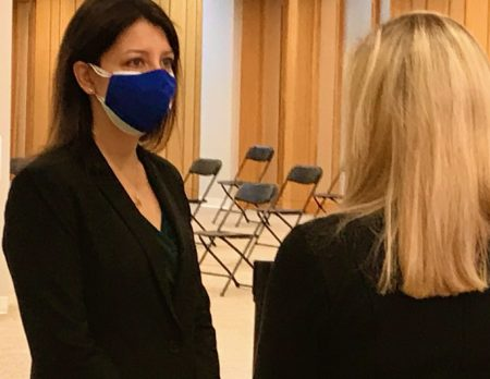 Dark-haired woman wearing face mask talks with blond-haired woman