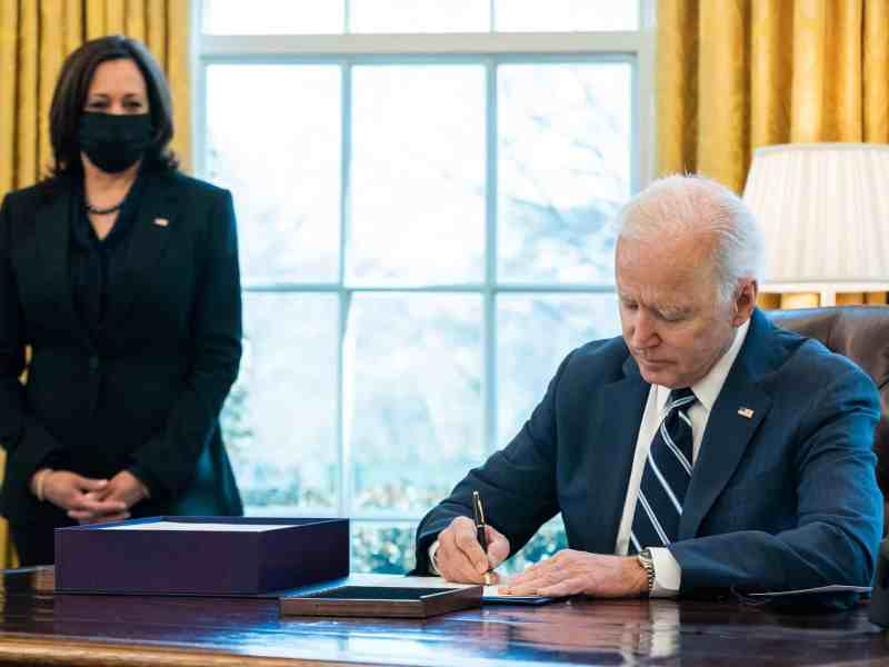 shows a man in a suit sitting at a desk signing a paper that strengthens Medicaid, in the background, a woman in a mask to prevent COVID transmission stands, watching.