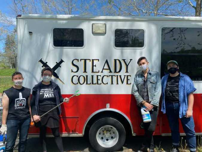 """shows a group of people wearing facemasks standing in front of an ambulance that now acts as a mobile needle exchange outlet. The words """"Steady Collective"""" are painted on the side with a logo of two crossed syringes"""