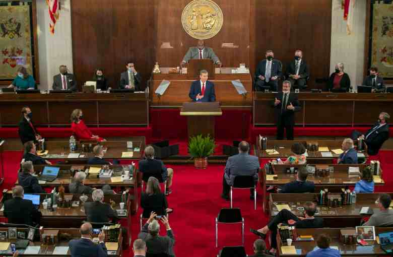 Shows a formal wood paneled legislative chamber with a man, Gov. Cooper, standing at the podium, others seated watching him.