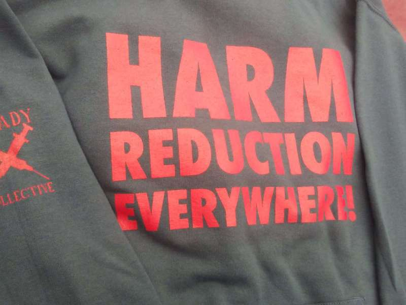 Shows a grey shirt with the words: Harm Reduction Everywhere printed in red. The organizations logo of two syringes crossed is is on the sleeve