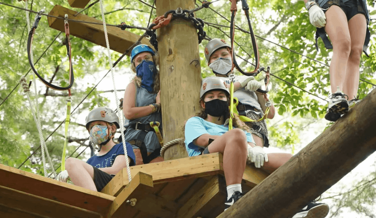 Shows girls on a climbing apparatus, they're wearing masks against the coronavirus, COVID-19