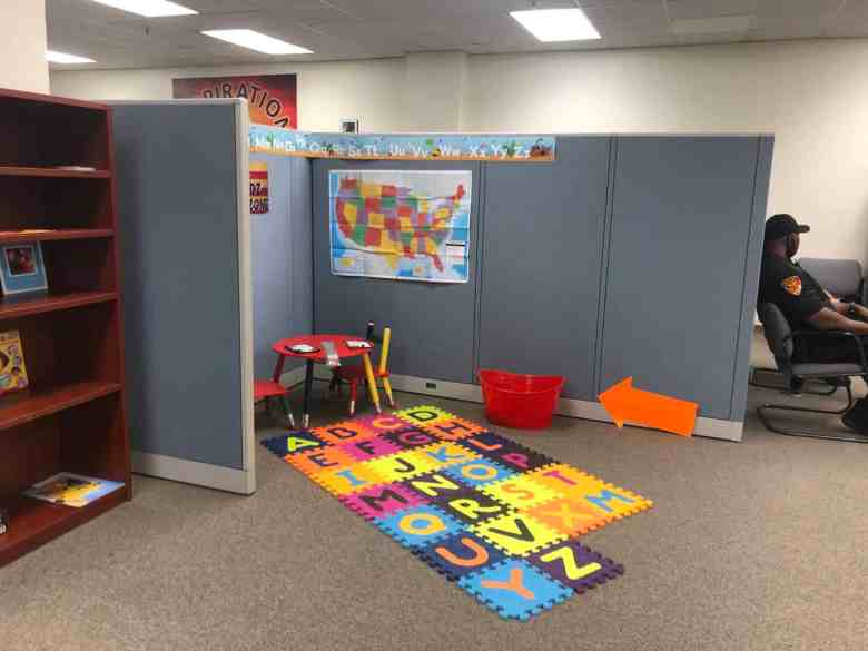 A brightly covered letter puzzle is on the floor of the children's play corner. In the corner is a red table and chairs, with a map of the United Stated on the wall.