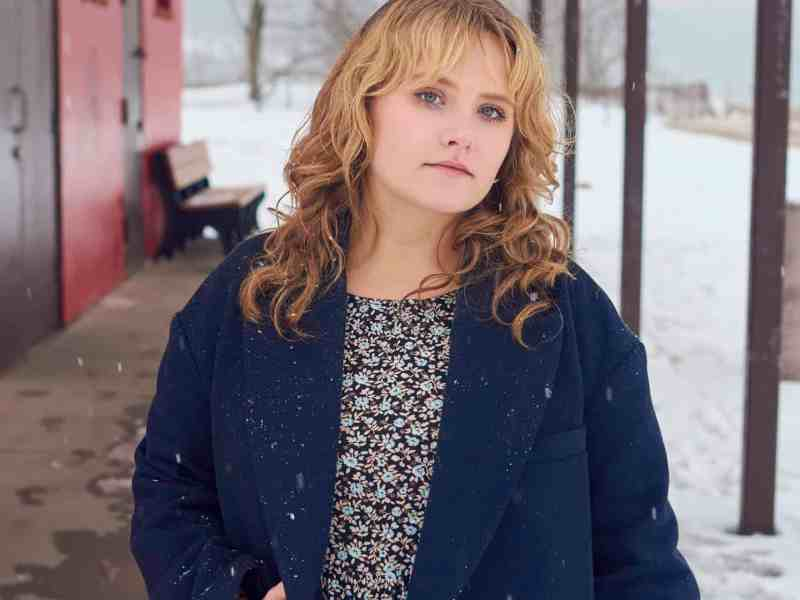 a young, blonde white woman stands in front of the camera in a dark blue coat