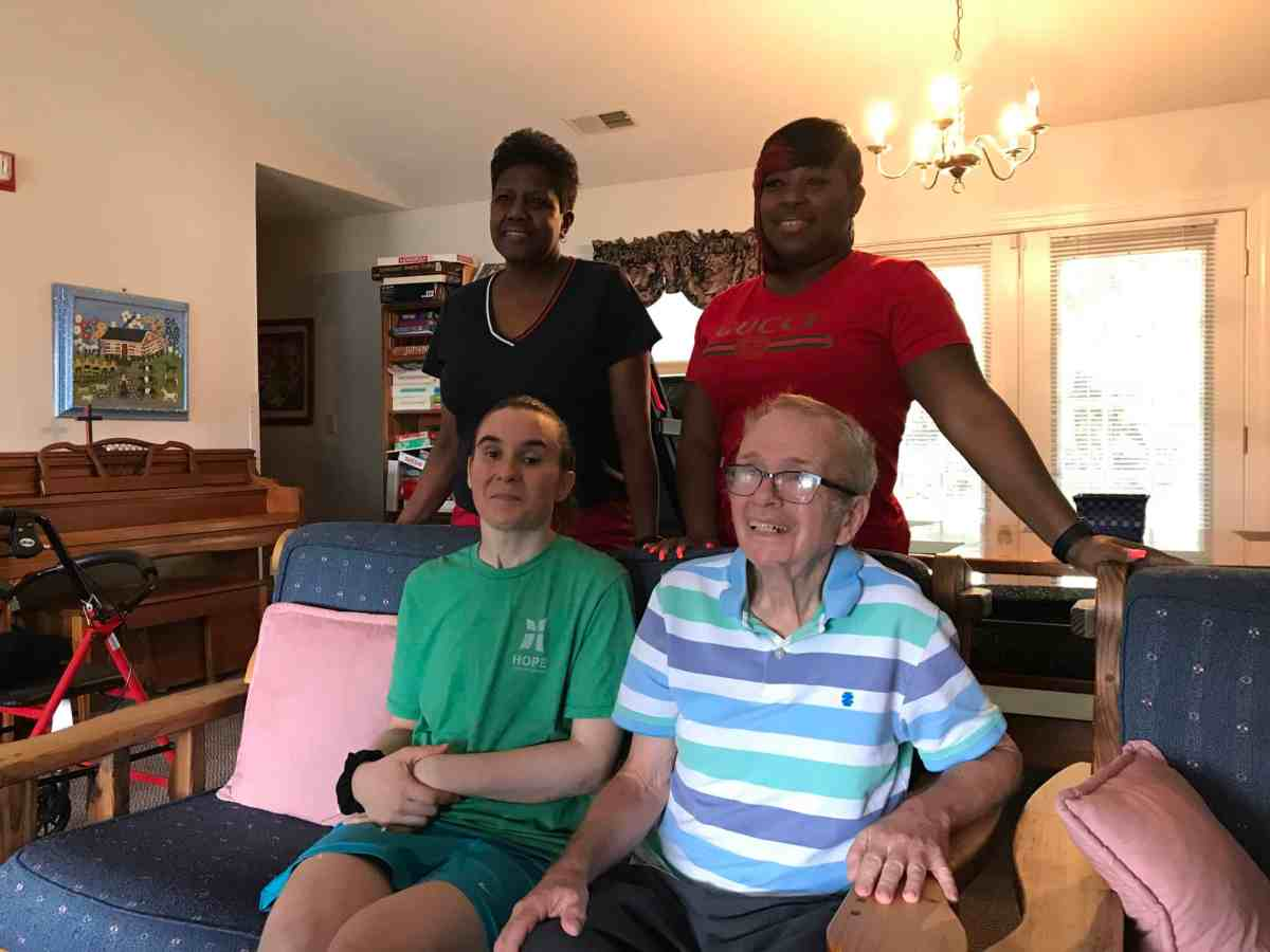 shows four people posing for a formal photo, two seated, two standing behind them. The two seated people are residents at a group home for people with intellectual / developmental disabilities and traumatic brain injury.