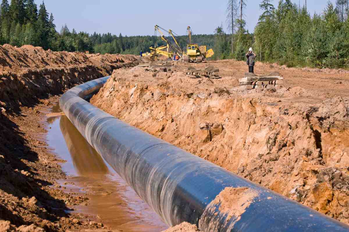 Shows a long, wide trench in the earth, with a large diameter pipeline in the muddy bottom
