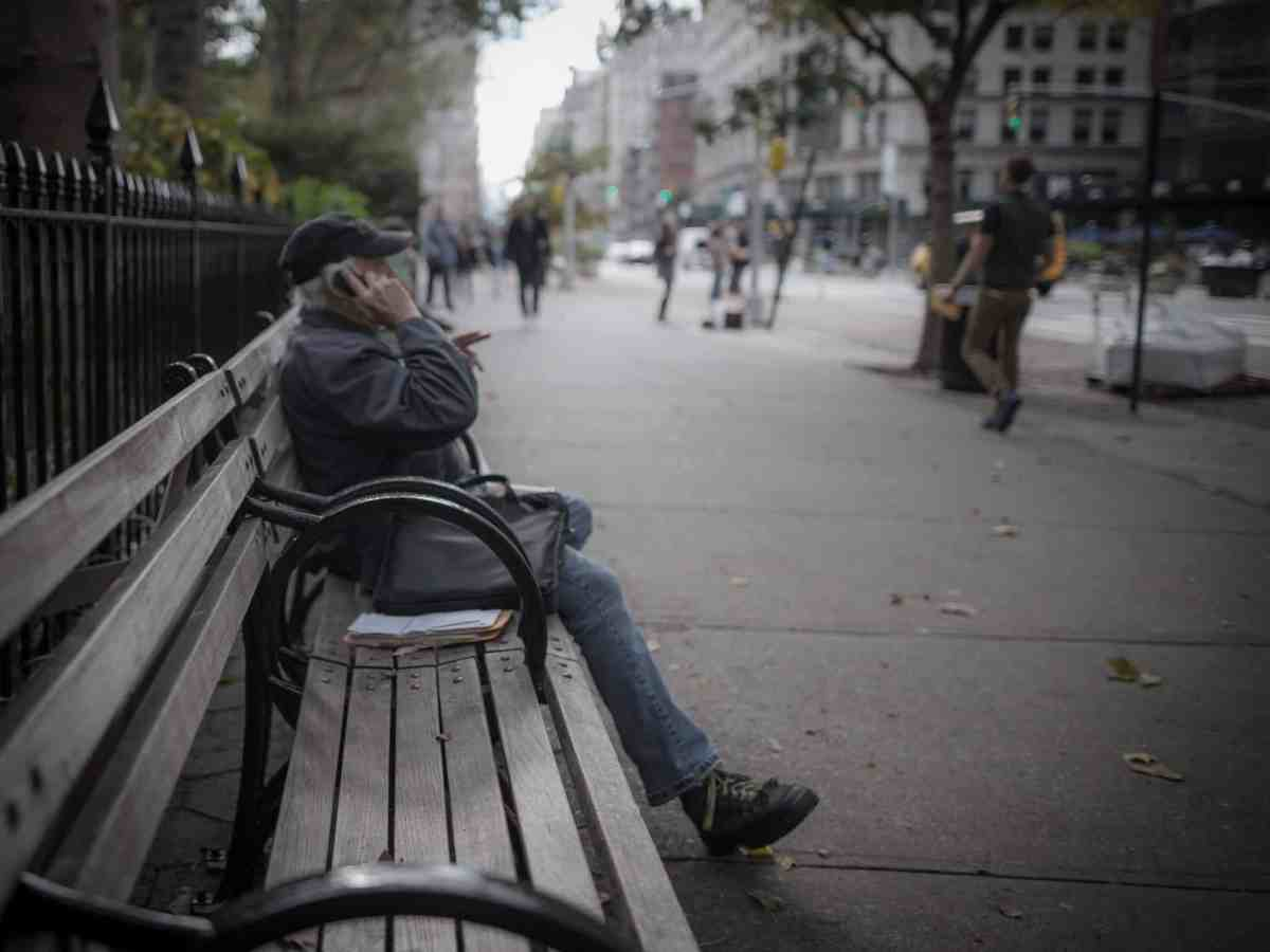 older white man with white hair, jacket and hat sits on a city bench talking on a cell phone