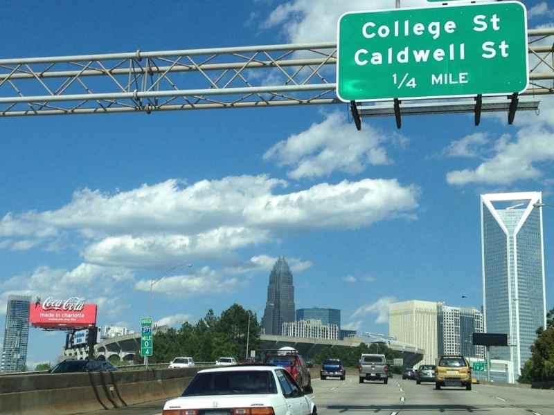 """Shows cars on a highway with signs overhead, the skyline in the distance and a Coca Cola sign reading """"made in Charlotte"""""""