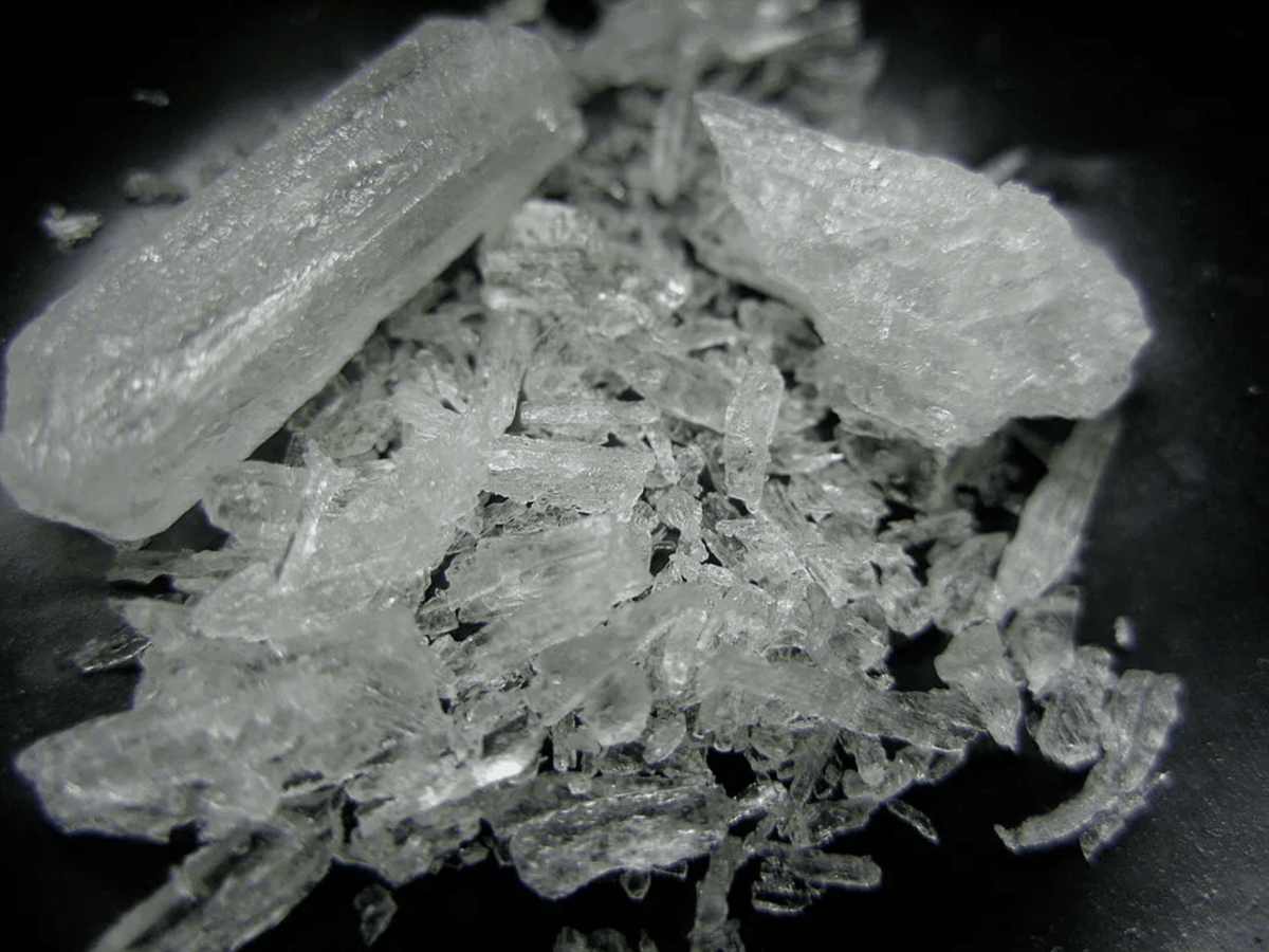 semi white crystal methamphetamine on a black background, both shattered pieces and full crystals