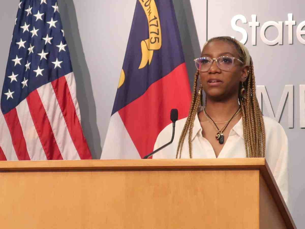 shows a young woman in glassed and braids standing behind a podium, speaking about COVID vaccination.