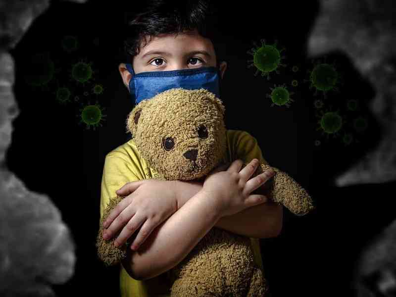 shows a little boy wearing a surgical maskholding a teddy bear behind him are images of the coronavirus