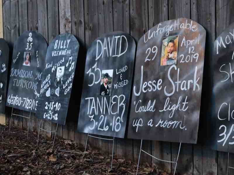 Black Cardboard tombstone shaped displays with hand-lettered messages and photos of people who died of overdose