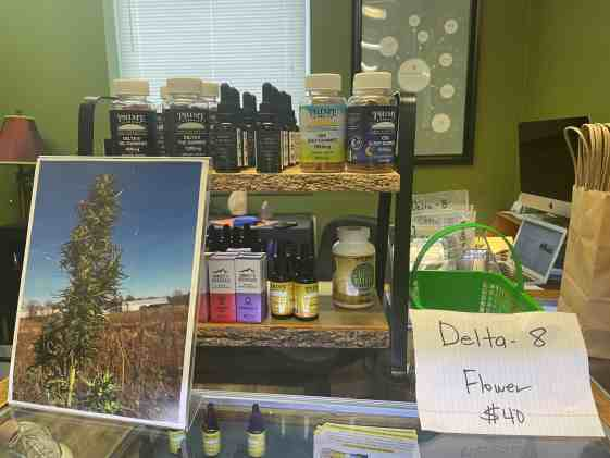 """Picture of products sold at dispensary lined up. On the right there is a paper that says """"Delta-8 Flower $40"""" on the left there is a picture of a hemp plant."""