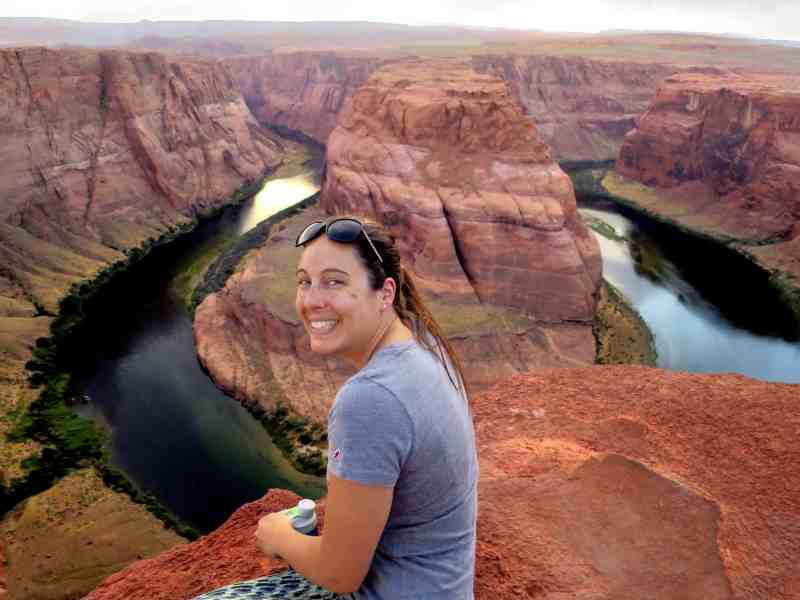 Shows a smiling woman sitting at the top of a cliff. Below her is a dramatic bend in a river at the bottom of a canyon.