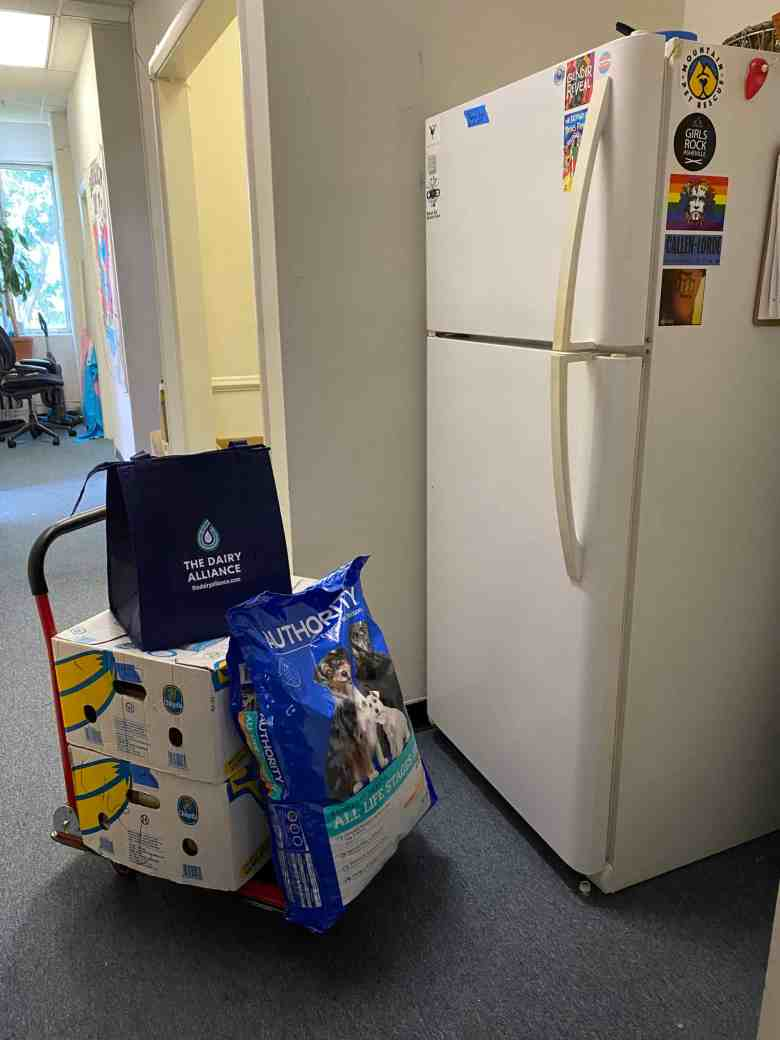 """There is a refrigerator on the right and on the left a trolley with banana boxes, cat litter and a bag with """"the dairy alliance"""" on it."""