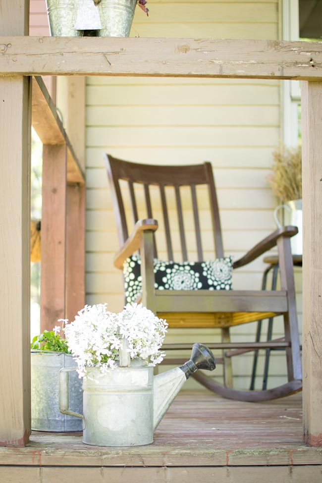 summer front porch rocking chair and galvanized watering can