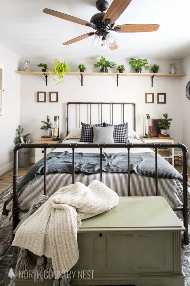 rustic winter guest bedroom with plant shelf and farmhouse bed frame