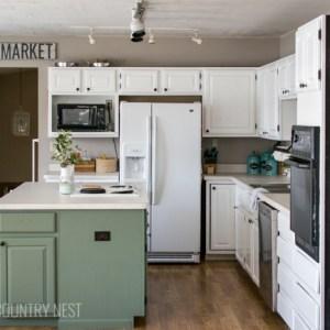 white kitchen cabinets, green island and chalkboard wall