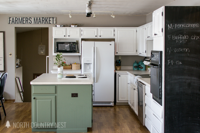 white kitchen cabinets, green island and chalkboard wall