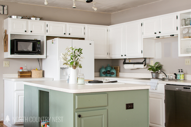 white kitchen cabinets with green island