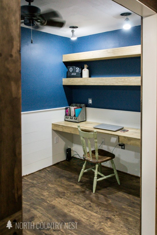 home office with plywood floors, floating shelves and shiplap