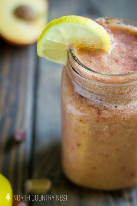 peach rhubarb smoothie with lemon slice in mason jar glass