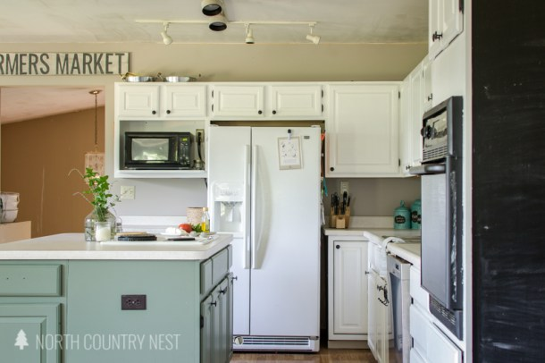 white kitchen cabinets with green painted island