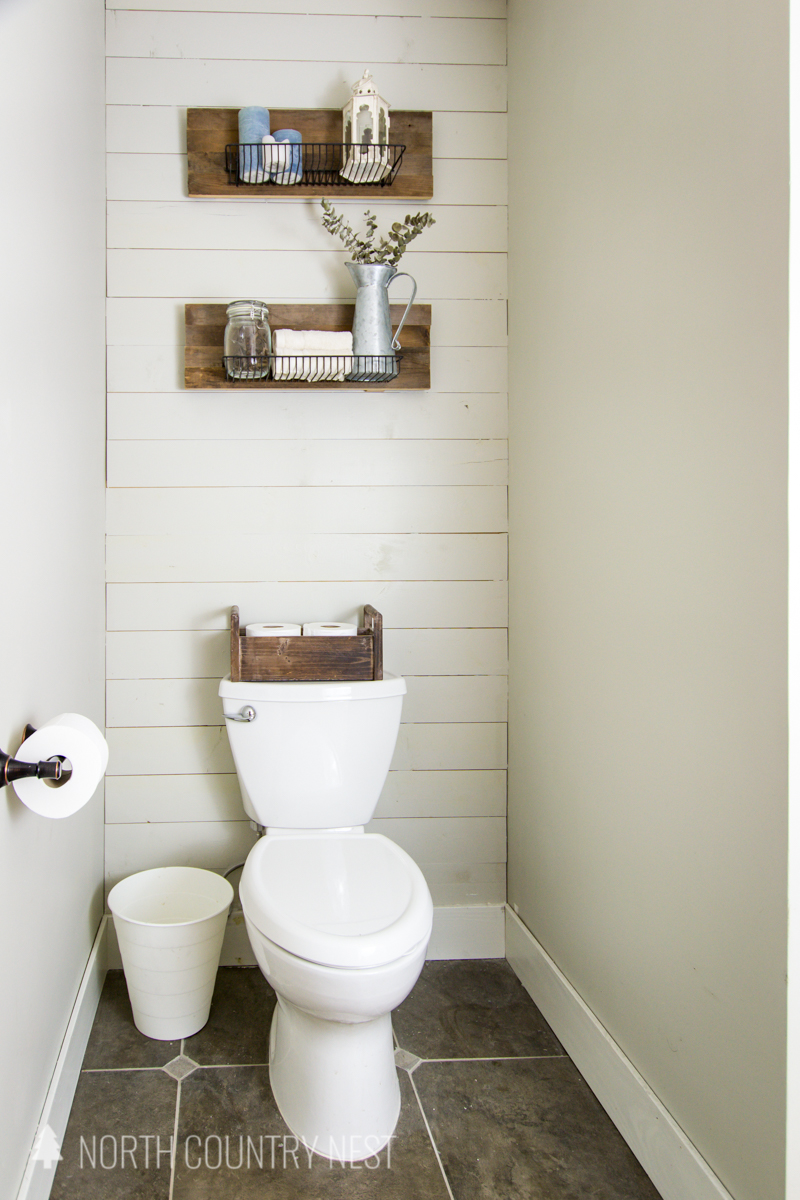 shiplap wall in bathroom with rustic industrial shelves