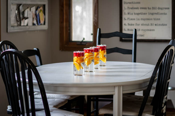 cylinder vases filled with cranberries and oranges