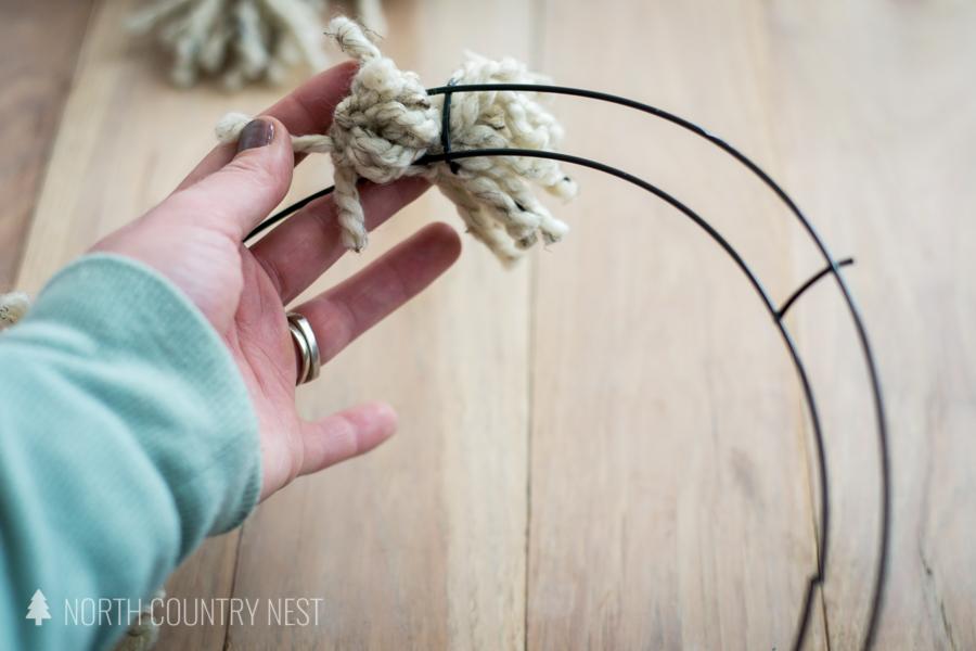 tying pom to wire wreath frame