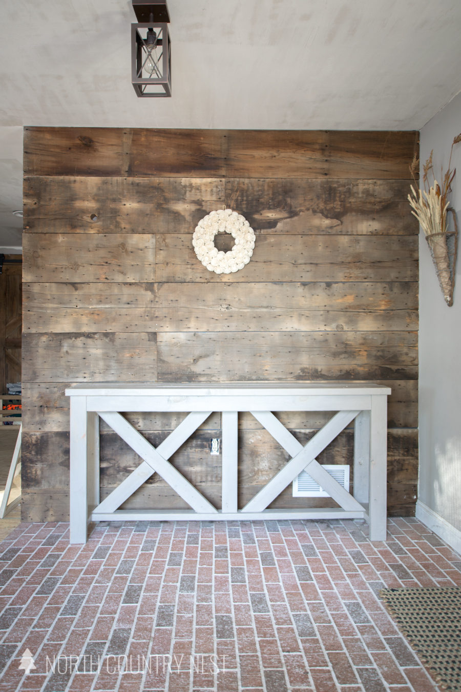 entryway table and wreath hung on barnwood wall