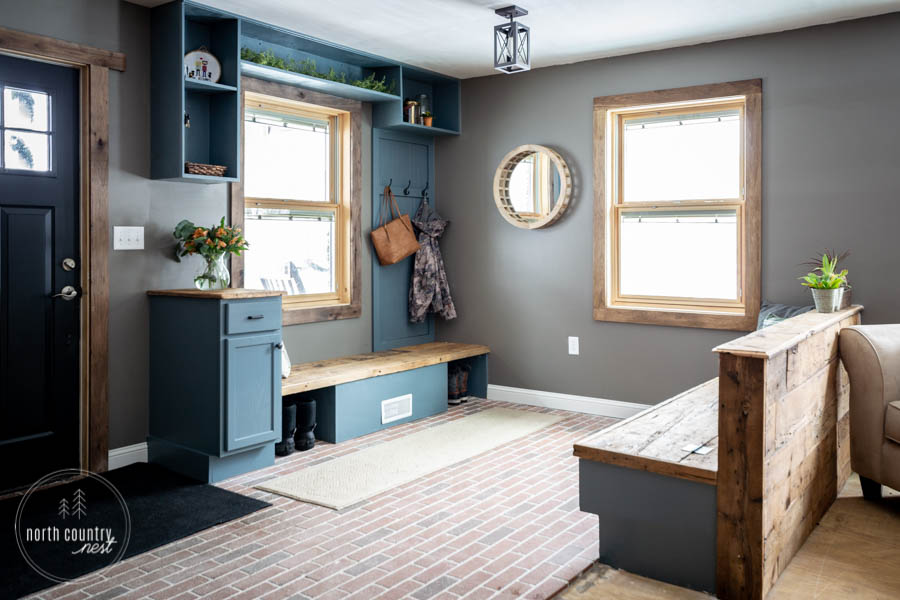 modern rustic entryway with blue built-ins and brick floor