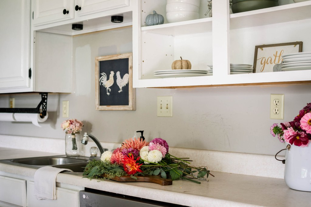 white kitchen with freshly cut flowers for fall