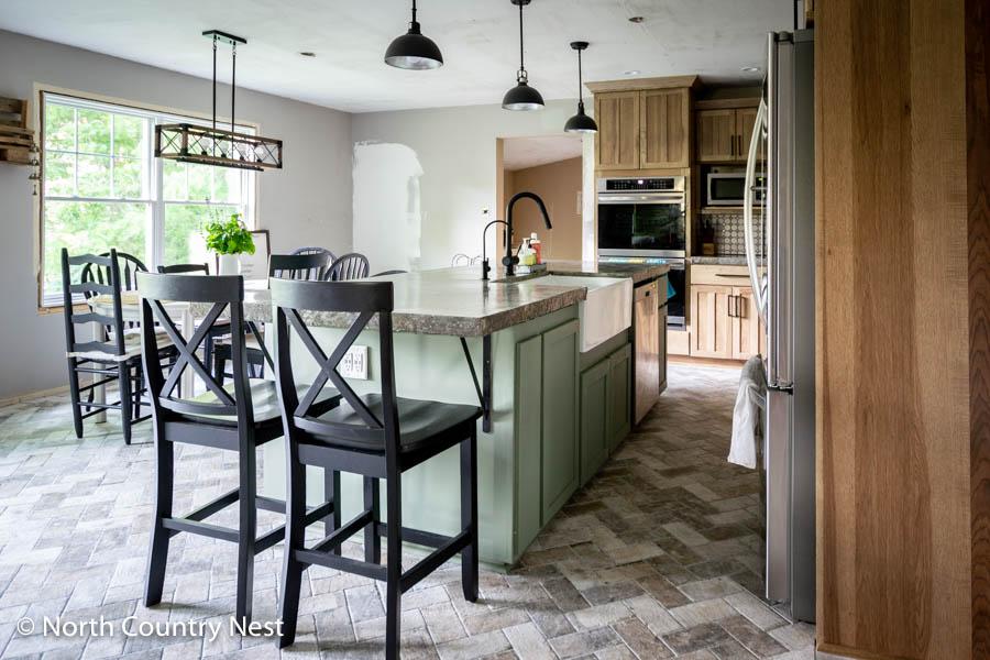 Herringbone kitchen floor tile with black barstools and a green custom kitchen island