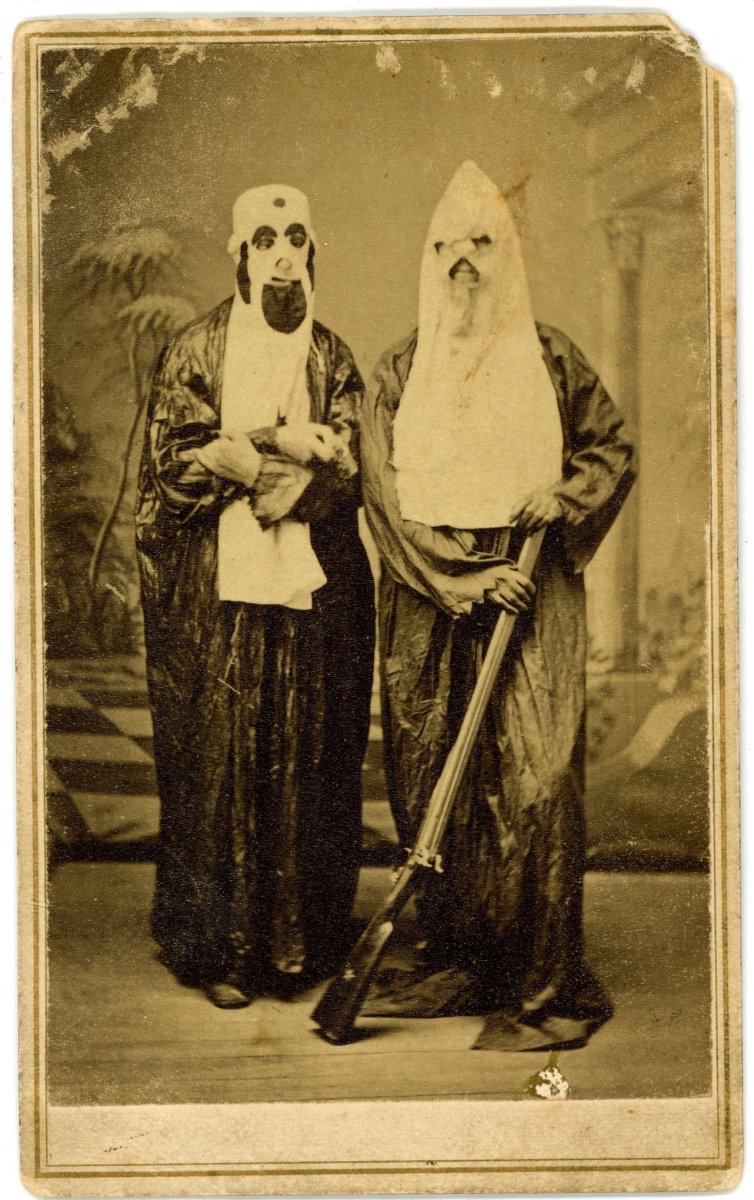 Two men wearing dark robes with white hoods pose for a photo. One is holding a rifle. Their faces are entirely obscured by their hoods.