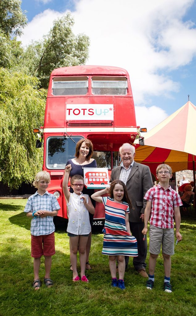 Sally Marks of TOTSUP and Terry Gilbert, a business advisor at North Somerset Enterprise Agency, celebrating the TOTSUP reward chart and app launch with (from left to right): Finn aged 7, Edie aged 6, Poppy aged 6 and Ben aged 7.