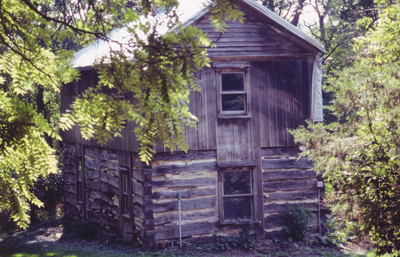 The Aslak Lie house prior to dismantling for preservation. The damaged roof is covered with a protective white tarp. Photo courtesy of Folklore Village.