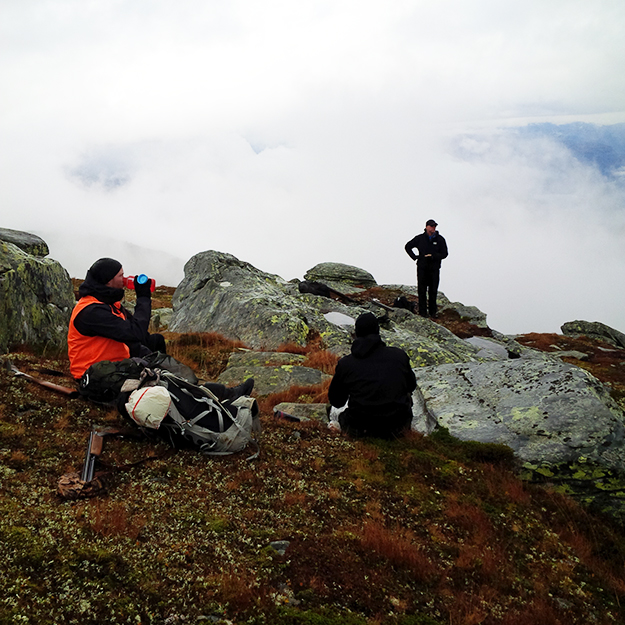 Photo: Nils Wanberg The hunters rest on a rocky hillside, as fog swirls behind.