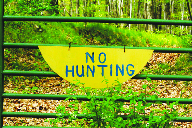 """A sign on a gate that says """"No Hunting"""""""