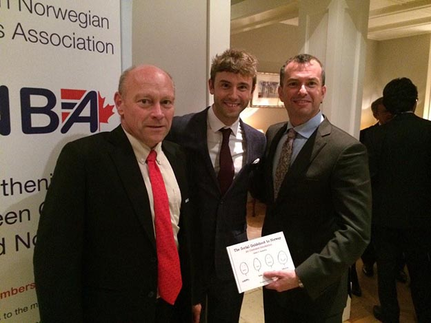 Photo: Artur Wilczynski / Twitter  Julien Bourrelle, center, with Artur Wilczynski, Lars-Kåre Legernes, and a copy of his book, at the Canadian Norwegian Business Association Christmas party.