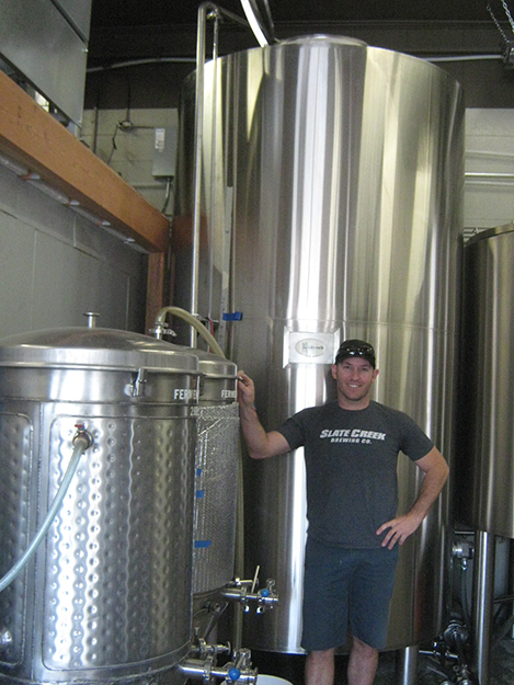 Photo: Barbara K. Rostad Co-owner Ryan Wing stands by both their old and new brewing systems. At left are their start-up barrels while behind him looms one from the 15-barrel-system installed October, 2014.