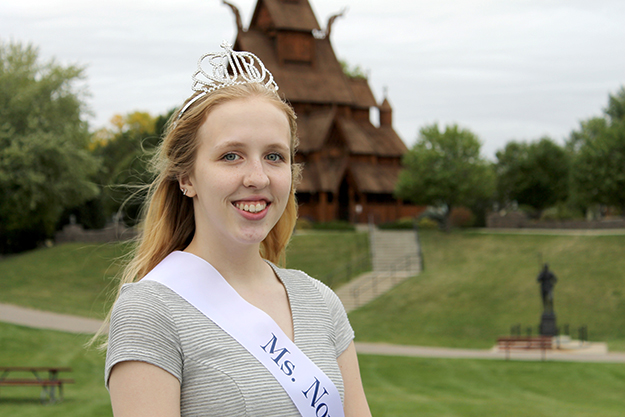 """Photo: Leann Mellum Jane Peterson, 2015's Ms. Norsk Høstfest, in front of the stave church at Minot's Scandinavian Heritage Association. The impressive high school senior is a survivor of bone cancer and a beekeeper who bottles and sells """"Buzz Off Honey,"""" and plans to become a nurse practitioner."""
