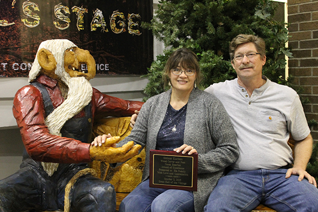 Photo: Leann Mellum The family of Steinar Karlsen with one of his creations and an award from Høstfest made in memory of Karlsen, who passed away this year. Karlsen had made many chainsaw carvings for Norsk Høstfest.