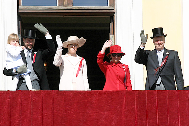Photo: Ernst Vikne / Wikimedia Commons The Royal House on the Palace balcony during the 17th of May parade in 2007. The current Royal House includes King Harald V of the German House of Schleswig-Holstein-Sonderburg-Glücksburg; his wife, Queen Sonja; Crown Prince Haakon, the King's son and the heir apparent; Crown Princess Mette-Marit, the King's daughter-in-law; and Princess Ingrid Alexandra, Crown Prince Haakon's eldest child. The Royal Family is larger, as it includes the Royal House and other children, grandchildren, step grandchildren, and siblings of the King, along with their spouses and widows or widowers.